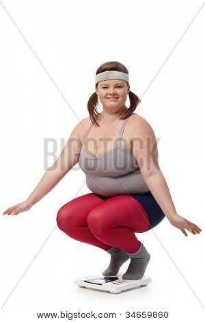 Fat woman squatting on scale, smiling happily.