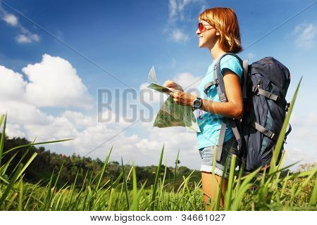 Young backpacker standing on a green meadow at sunny day and looking to somewhere