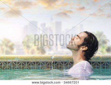 Young good looking man in a swimming pool playfully spitting water out of his mouth