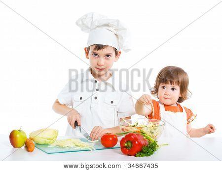 Two smiling kids mixing salad
