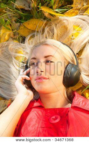 beauty girl listening music in the park