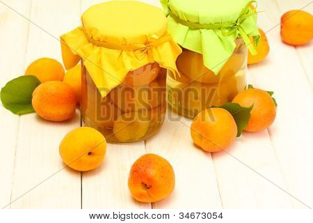 canned apricots in a jars and ripe apricots on white wooden table