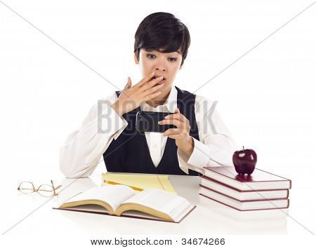 Pretty Mixed Race Female Student at Desk with Books Has Shocked Look from Cell Phone Message Isolated on a White Background.