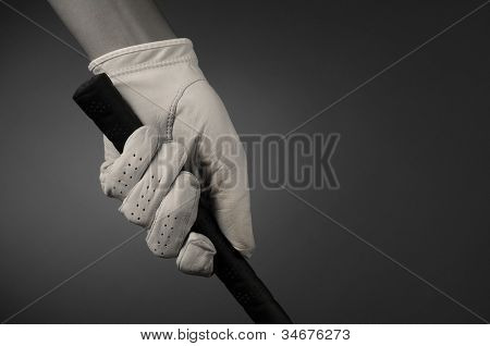Closeup of a golfers hand on the handle of a golf club. Horizontal format on a light ot dark background. Slight sepia toning for an old fashioned look.