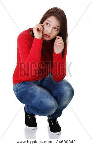 Young woman is whipping tears in squat position. Isolated on white background.