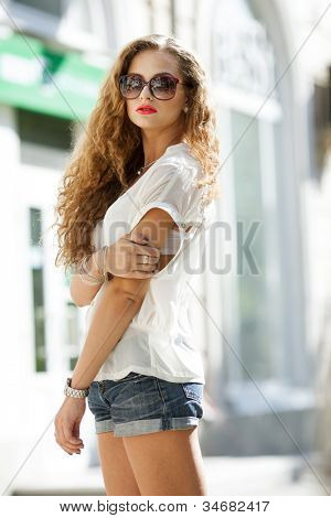 Summer portrait of a beautiful young Caucasian girl with curly hair