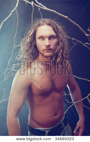 Long haired naked man with scary eyes in the forest, Halloween theme