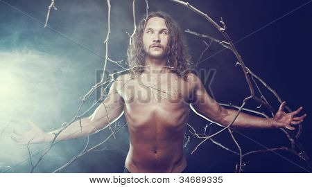 Muscular naked man with scary eyes in the forest, Halloween theme
