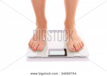A picture of female feet standing on a bathroom scales over white background