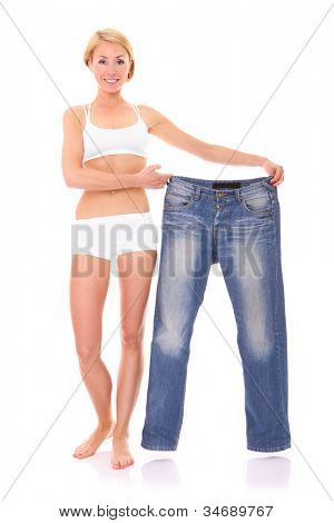 A picture of a young fit woman showing too big jeans as diet effects over white background