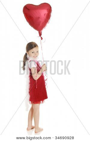 A barefoot elementary girl smiling back over her shoulder while holding a heart-shaped balloon.  She's dressed in red with a fluffy white boa and strands of hearts.  On a white background.