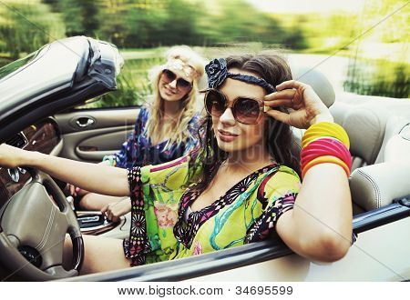 Two young women driving a car