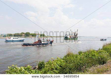 Urk, The Netherlands - May 19: Decorated Fishing Ships Are Leaving The Harbor During A National Fish