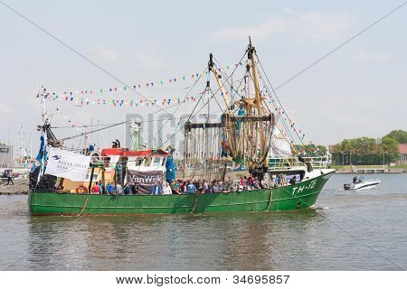 Urk, The Netherlands - May 19: A Decorated Fishing Ship Is Leaving The Harbor During A National Fish