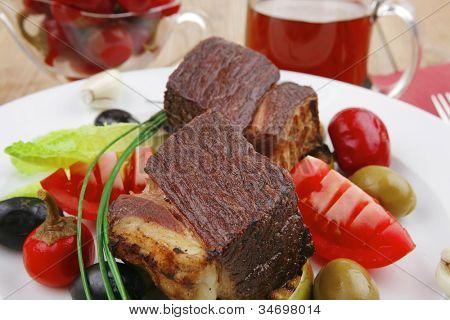 asar carne: ternera bistec (cerdo) con jugo, manzanas al horno, tomate, aceitunas verdes y negras