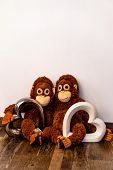 Two Soft Toy Monkeys Sit Arm In Arm On The One With Two Glass Hearts poster