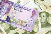 A Close Up Image Of A Colorful One Rial Bank Note From Oman On A Bed Of Chinese One Yuan Bank Notes  poster