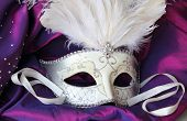stock photo of incognito  - A mardi gras masquerade ball mask on a dress made from purple satin - JPG