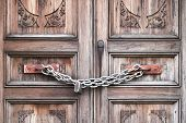 A Double Wooden Door Chained Closed. Closeup Of Old Wooden Door With Closed Padlock On A Chain. A Ch poster