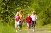 Family jogging for sport outdoors with the kids on summer day