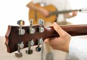 stock photo of guitarists  - Guitar lesson or two musicians playing together shot from behind one guitar with shallow focus - JPG