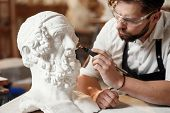 Male Sculptor Repairing Gypsum Sculpture Of Womans Head At The Working Place In The Creative Artisti poster