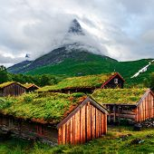 Typical norwegian old wooden houses with grass roofs in Innerdalen - Norways most beautiful mountai poster