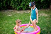 Kids Having Fun Party Swimming In Back Yard Pool. Funny Children Bathing In The Outdoor Pool. Happy  poster