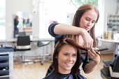 Hairdresser cutting client's hair in beauty salon.