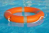 Orange Lifebuoy Pool Ring Float On Blue Water. Life Ring Floating On Top Of Sunny Blue Water. Life R poster