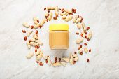 Creamy Peanut Paste In Glass Jar With Yellow Cap And Peanuts In The Shell And Peeled Peanuts. Creamy poster