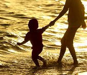 Boy With Mom At The Seaside At Sunset. poster