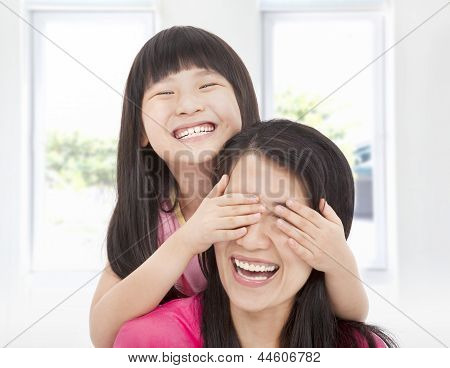 Happy Little Girl Cover Her Mother Eyes For Fun