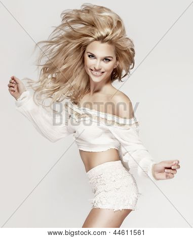 Fashionable Blonde Smiling Lady Jumping, Looking At Camera.