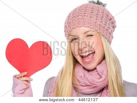 Portrait Of Girl In Winter Clothes Showing Heart Shaped Postcard