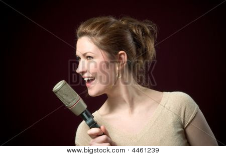 Beautiful Redhead Model Singing Into Gold Microphone