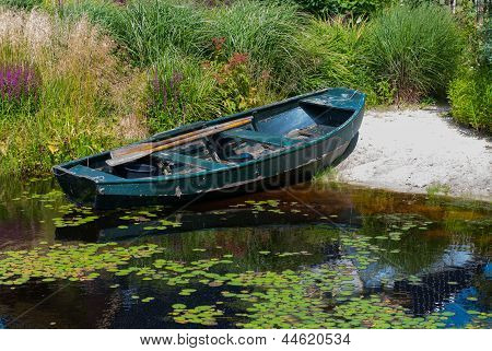 Rowboat In A Garden Pond