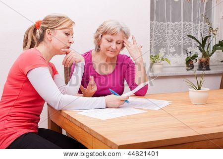 Two Women Pondering Over Documents