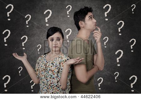 Confused Couple With Question Marks On Blackboard