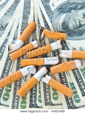 Cigarette Butts Laying On Money