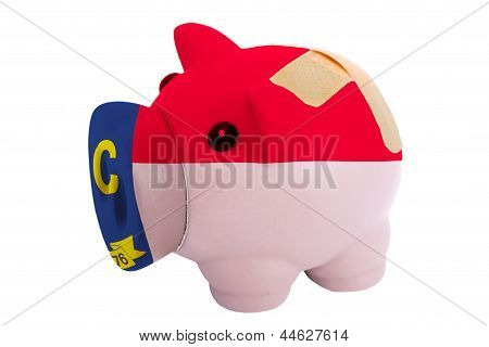 Closed Piggy Rich Bank With Bandage In Colors Flag Of American State Of North Carolina
