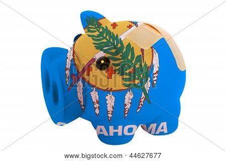 Closed Piggy Rich Bank With Bandage In Colors Flag Of American State Of Oklahoma