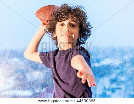 Young Child Playing Football Inside His House Because Of A Rainy Day