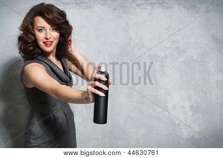 Beautiful girl laying fixes using hairspray