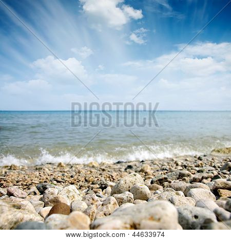 Ones And Sea Wave Over Cloudy Sky