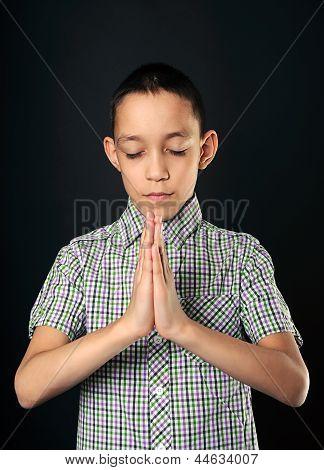 Praying Boy Closed Eyes Over Black