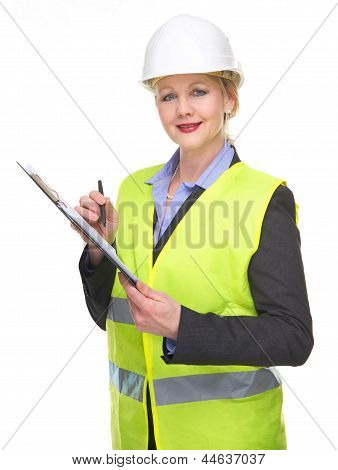 Portrait Of A Businesswoman In Safety Vest And Hard Hat Writing On Clipboard
