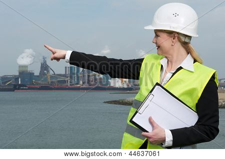 Female Inspector In Hardhat And Safety Vest Pointing At Industrial Site