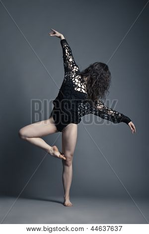 Modern style dancer posing on grey background