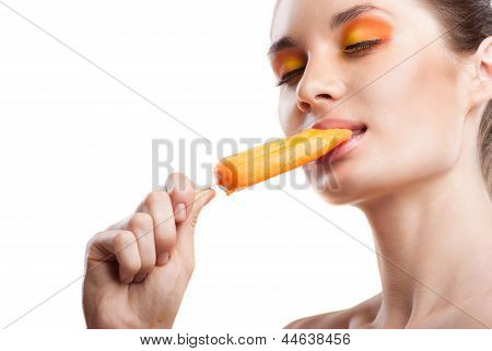 Woman eating orange ice-cream and having fun